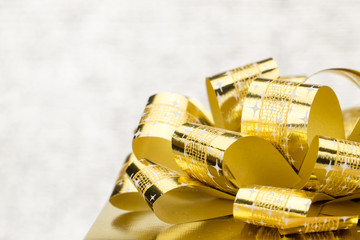 Close up Golden present box with big bow at bokeh white blur bac