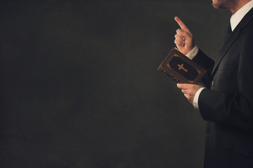Man with a Bible and a wagging finger