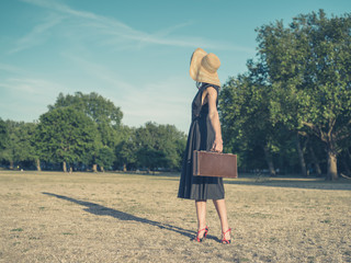 Elegant young woman with briefcase standing in park