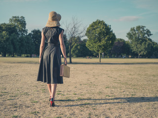 Elegant woman walking in park with briefcase
