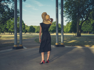 Young woman wearing hat at bandstand in park