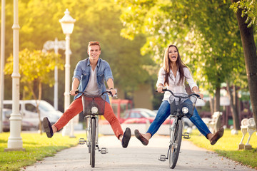Happy funny couple riding on bicycle