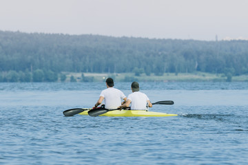 Two boys in sport kayak paddles on the water