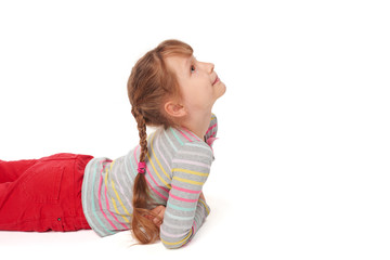 Side view of smiling child girl lying on the floor