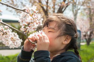 花の香りを嗅ぐ子供