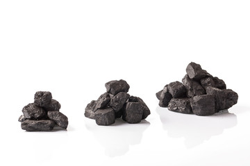 Three small piles of black coal on a white glossy background