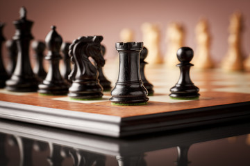 Traditional Staunton black chess pieces carved in genuine ebony in focus standing on elm burl and bird's eye maple superior chessboard just before the game