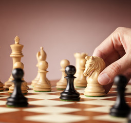 Male hand moving the white chess knight in focus in the middle of a chess game