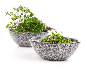 Thyme in bowl isolated on white background.
