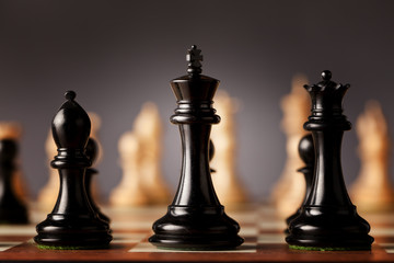 Behind the scenes - black chess king, queen and bishop in focus standing on a wooden chessboard facing the white chess pieces before the game