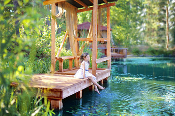 Girl sitting on a wooden bridge at the pond
