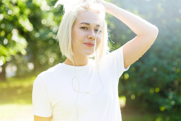 Girl with platinum blond hair in white t-shirt in a park