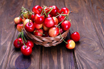 Ripe cherries on wooden table in a basket