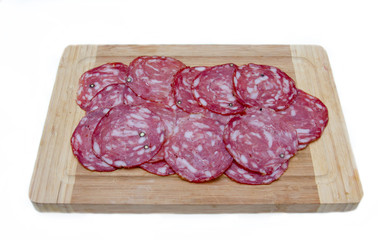 Slices of salami on cutting board on white background