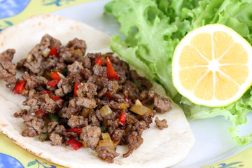 healthy eating: grilled beef taco with vegetables, salad and lemon served on plate