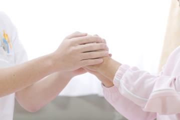 患者の手を握る医療スタッフ