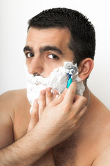 Italian or middle eastern looking man in his thirties shaving on white background