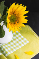 sunflowers in a vase on a black wooden background