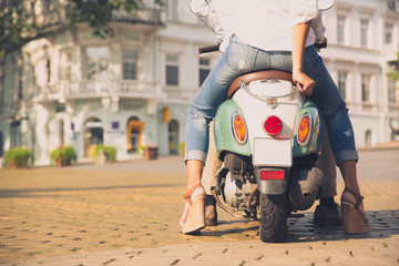Back view portrait of a scooter with female legs in old european town