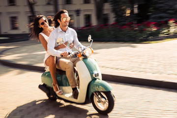Cheerful young couple riding a scooter