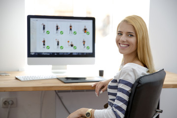 Smiling young girl sitting at her workplace