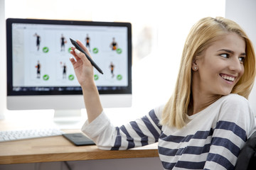 Young girl pointing pen on monitor