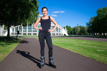 young woman on roller skates in summer park