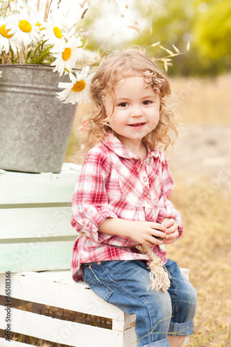 Cute Baby Girl Sitting On Crates With Flowers Outdoors Stock Photo