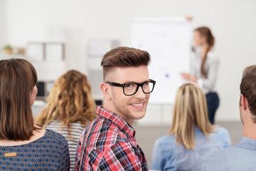 mann in einem seminar schaut lächelnd zurück