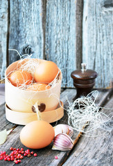 Three eggs in the wooden box with red pepper and pepper-pot on the vintage background