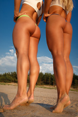 Two girls in swimsuits posing on the beach.