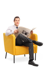 Man sitting in an armchair and holding a newspaper