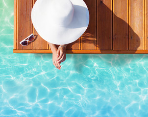 Summer holiday fashion concept - tanning woman wearing sun hat on a wooden pier view from above