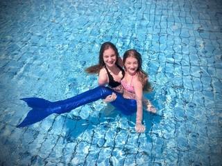 Ragazze in piscina con coda da sirena