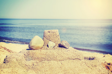 Vintage retro toned simple sandcastle on a beach, summer holiday