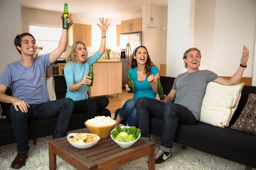 Sports friends fans drinking beer at home celebrating a game on TV