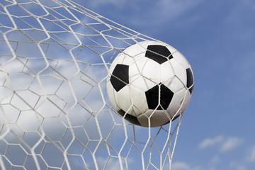 soccer ball in the net on blue sky background