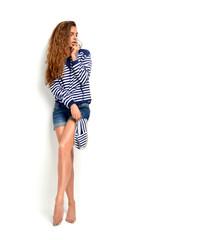 brunette woman holding summer flip flops in blue stripes and jea