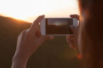 Young woman photographing sunset with Smart phone camera