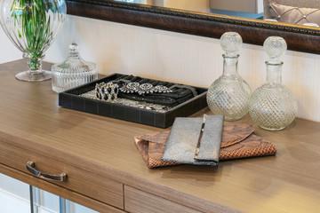 handbag and jewelry set on a dresser table in a contemporary roo