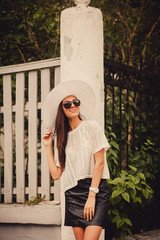 portrait of a cute girl in sunglasses and a hat in the city