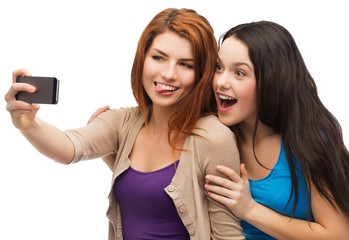 two smiling teenagers with smartphone