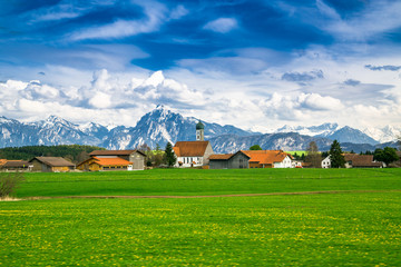 Kirche mit Bergen und saftiger Wiese