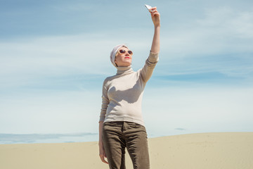 Woman holds a smartphone and makes selfie