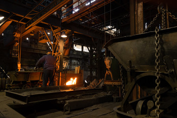 Foundry Worker Manipulating With Molten Metal