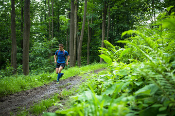 middle age trail runner training in the woods on the muddy track