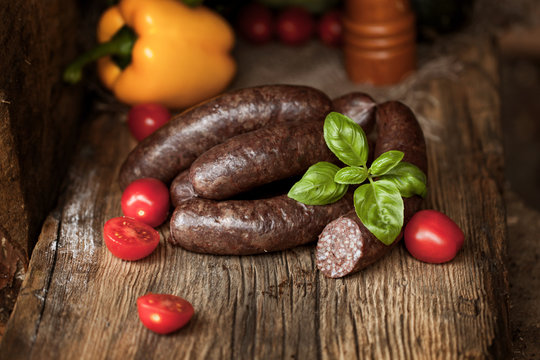 Black pudding, with cut slices, on chopping board over stone background. Krupniok really Polish black pudding.