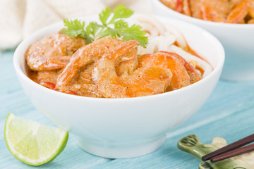 Thai Prawn Curry with Noodles - Thai red curry with prawns served with rice noodles in a white bowl.