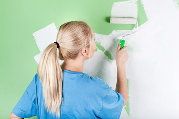 Young woman paints the wall