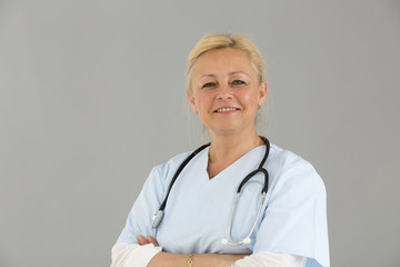Close up portrait of blond female self confident doctor with crossed arms smiling and looking at the camera
